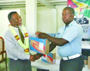 Prime Minister Hinds presenting a laptop to Ronald Thomas in Plaisance