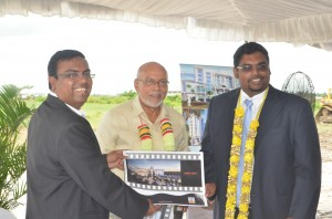 President Donald Ramotar and acting Tourism Minister Irfaan Ali being presented with a copy of the hotel plan