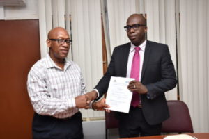 University of Guyana's Deputy Vice Chancellor, Academic Engagement Dr Michael Scott pose with Project Manager of the CSSP Clement Henry after the signing of the contract for  a survey on the prisons of Guyana